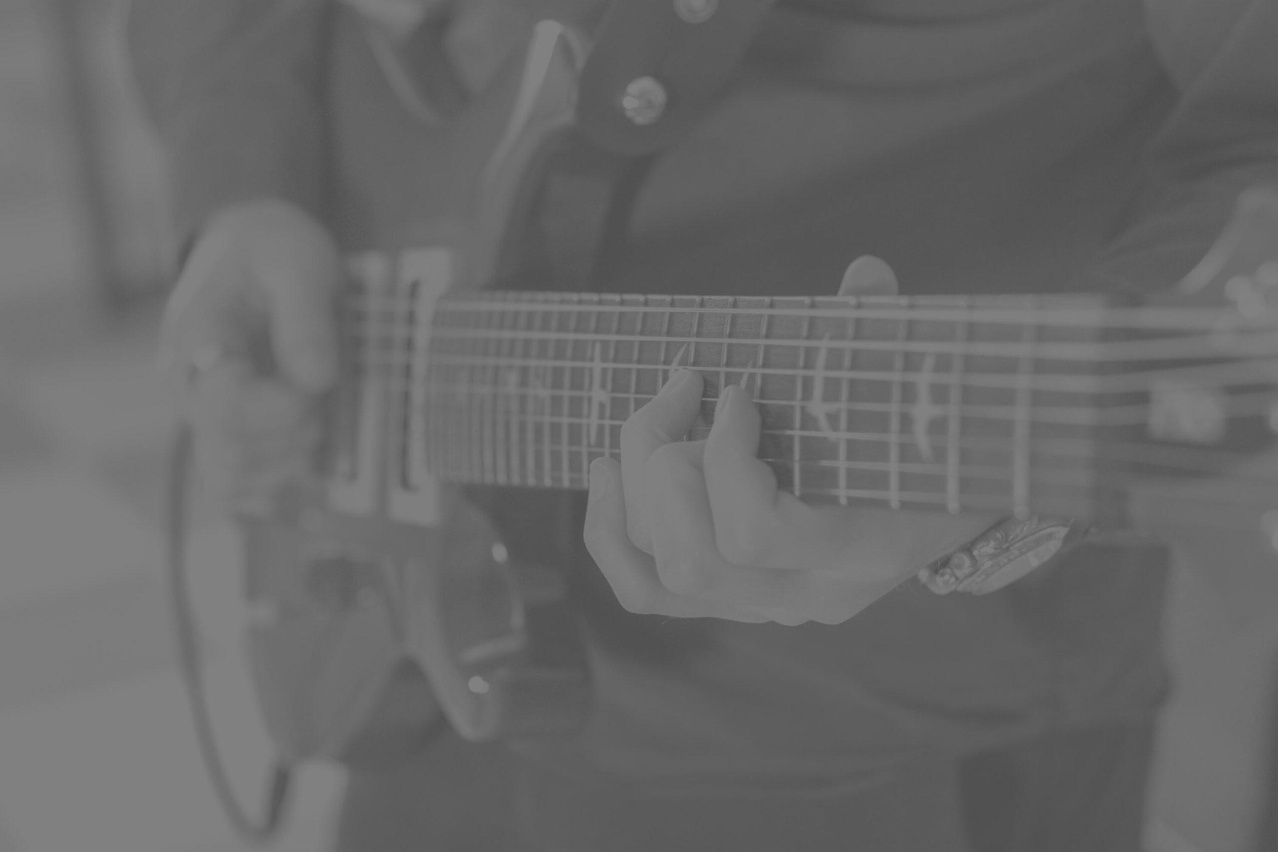 Lähikuva kitaraa soittavasta ihmisestä